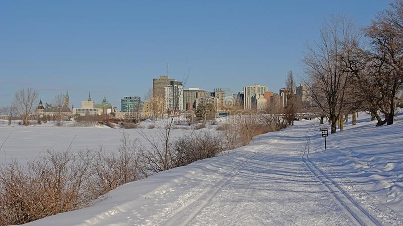 Sjam winter hiking trail along Ottawa river zith the city in the distance royalty free stock photos