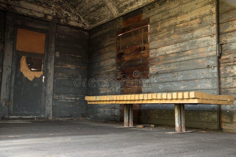 Sjaskig gammal trävagn från insidan, med bänken arkivbilder