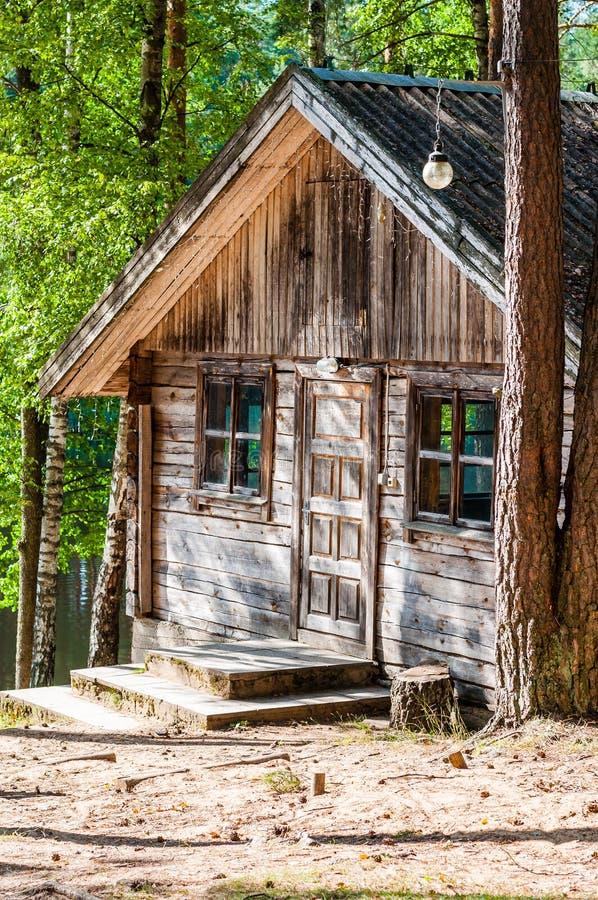 Sjofel oud traditioneel blokhuis met houten deuringang en twee vensters van beide kanten stock foto