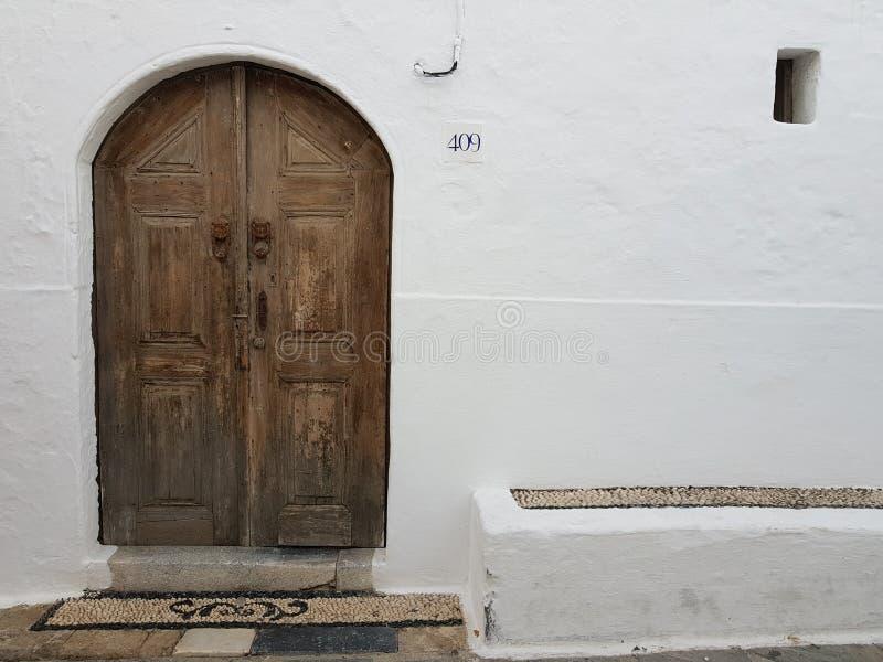 Sjofele houten deur van een wit oud huis op de straat van een oude greecstad royalty-vrije stock foto's
