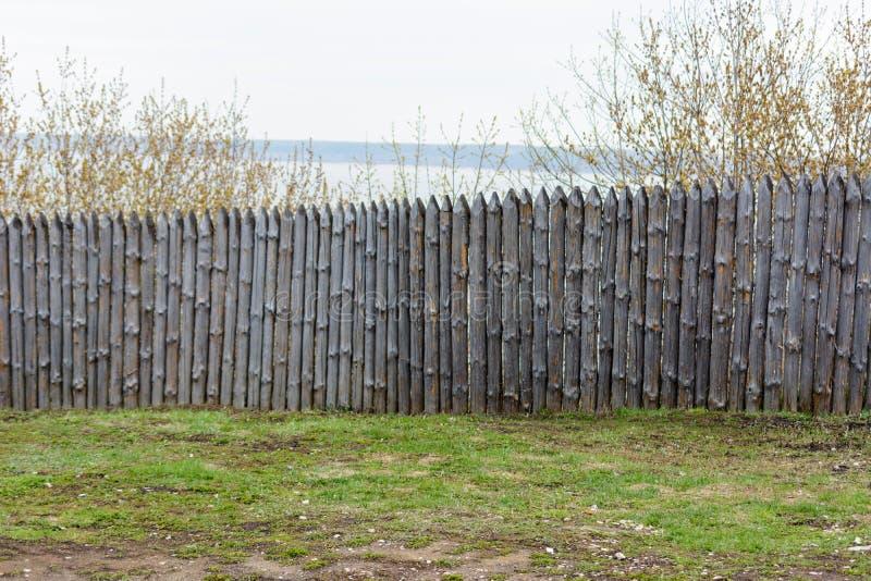 Sjofele omheining in de zonnige de lentedag Achtergrondtextuur van oude grijze houten omheining van gehele logboeken met knopen stock foto