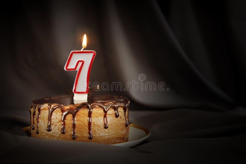 Sju år årsdag Födelsedagchokladkaka med den vita brinnande stearinljuset i form av nummer sju royaltyfri bild