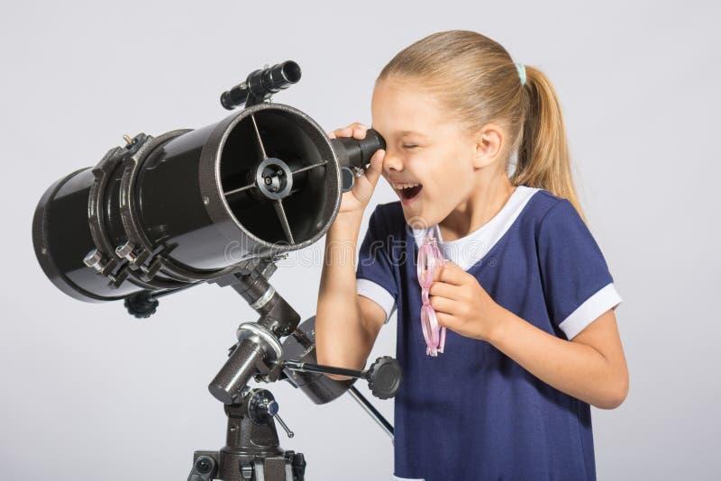 Sju-år flicka med intresse och öppet se för mun in i reflektorteleskopet och blickar på himlen royaltyfri foto