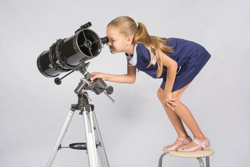 Sju-år flickaanseende på en stol och blickar som är löjliga i okular av teleskopreflektorn royaltyfri foto