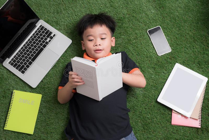 Sju år gammalt barn som läser en bok som ligger på gräset arkivfoton