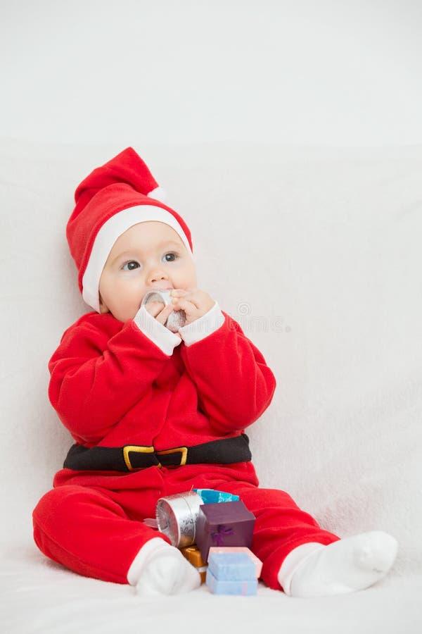 Sju gamla månader behandla som ett barn flickan i den Santa Claus klänningen arkivfoto