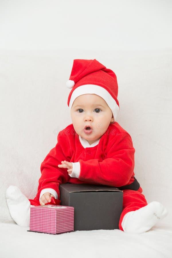 Sju gamla månader behandla som ett barn flickan i den Santa Claus klänningen arkivbilder