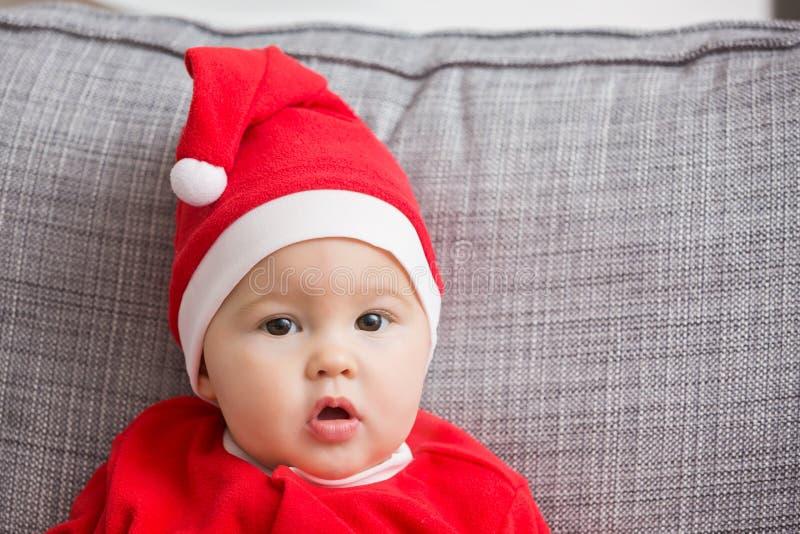 Sju gamla månader behandla som ett barn flickan i den Santa Claus klänningen royaltyfri bild