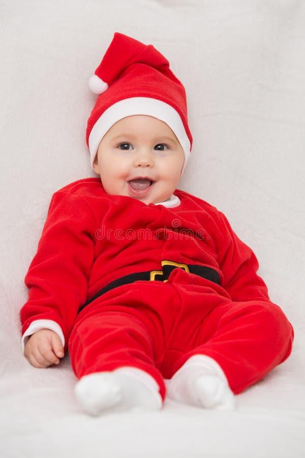 Sju gamla månader behandla som ett barn flickan i Santa Claus klänningsammanträde på en whi royaltyfria bilder