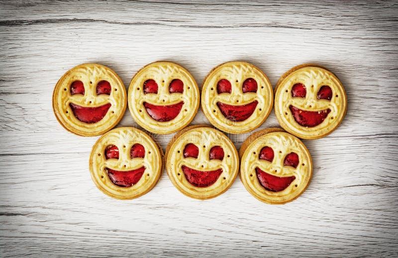 Sju runda kex som ler framsidor, humoristiskt mattema royaltyfri bild