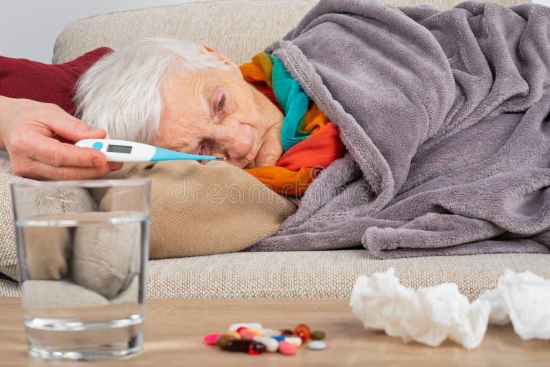 Sjuk äldre kvinna på soffan arkivbild