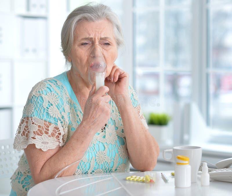 Sjuk äldre kvinnadanandeinandning royaltyfri fotografi