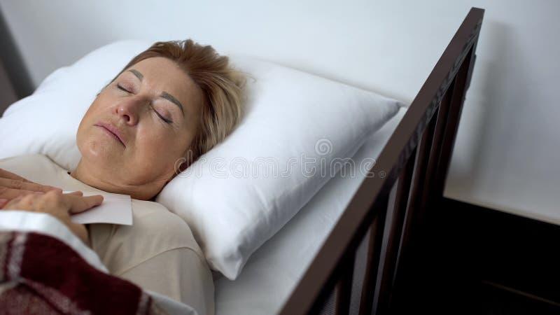 Sjuk äldre patient som sover i sjukhussäng och rymmer familjfotoet, hopp fotografering för bildbyråer