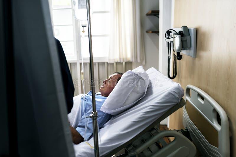Sjuk åldring som blir på ett sjukhus arkivfoto