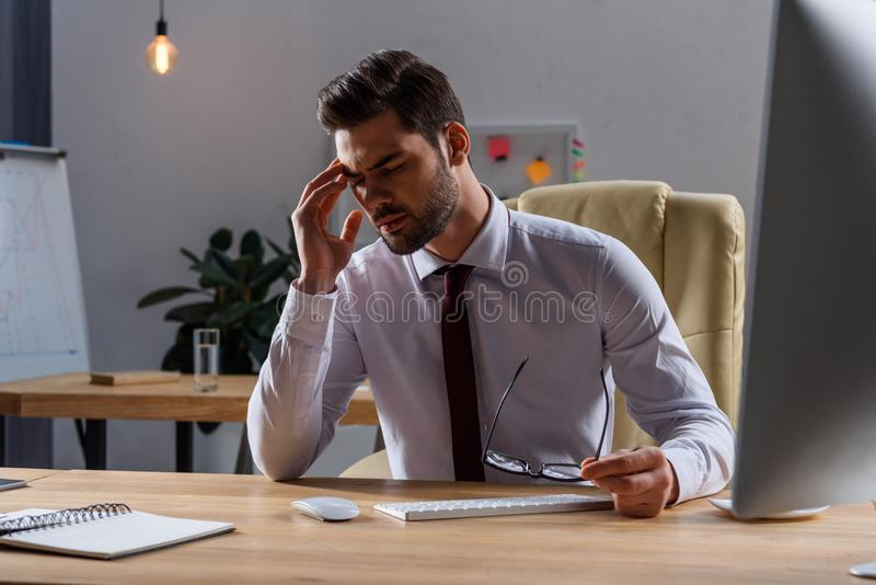 sjuk affärsman som har huvudvärk, medan arbeta i afton arkivfoton