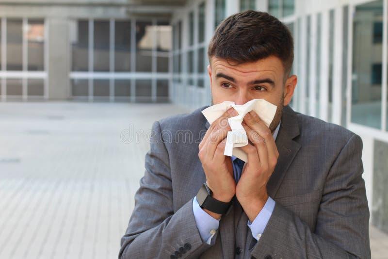 Sjuk affärsman som i regeringsställning blåser hans näsa royaltyfri foto