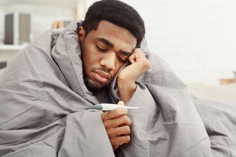 Sjuk afrikansk amerikanman som slås in i filten som rymmer termometern royaltyfri foto