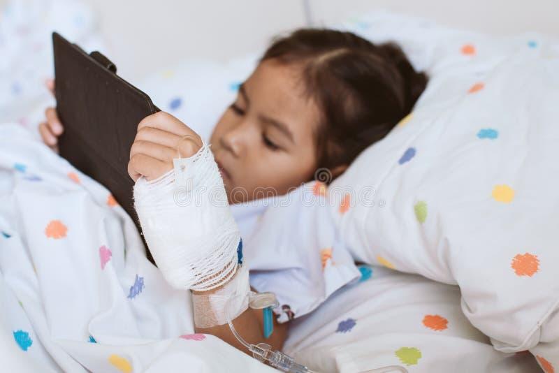 Sjuk asiatisk flicka för litet barn som använder den digitala minnestavlan royaltyfri bild