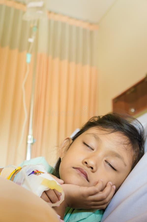 Sjuk asiatisk liten flickasäng vilar patienten i sjukhus arkivbild