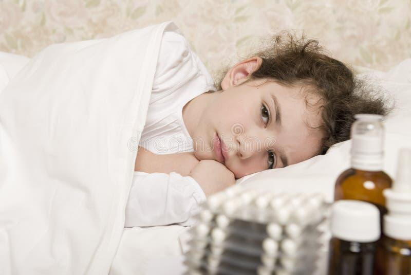 Sjuk barnflicka i en säng fotografering för bildbyråer