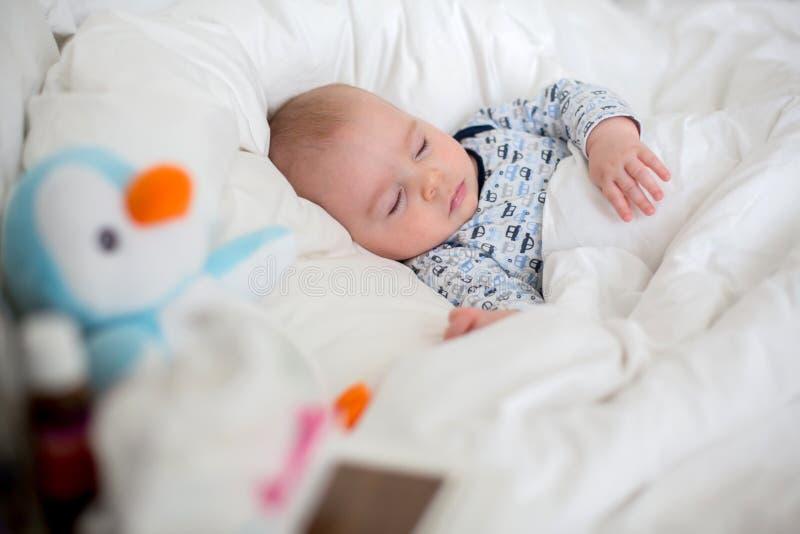 Sjuk barnpojke som ligger i säng med en feber som hemma vilar arkivfoto