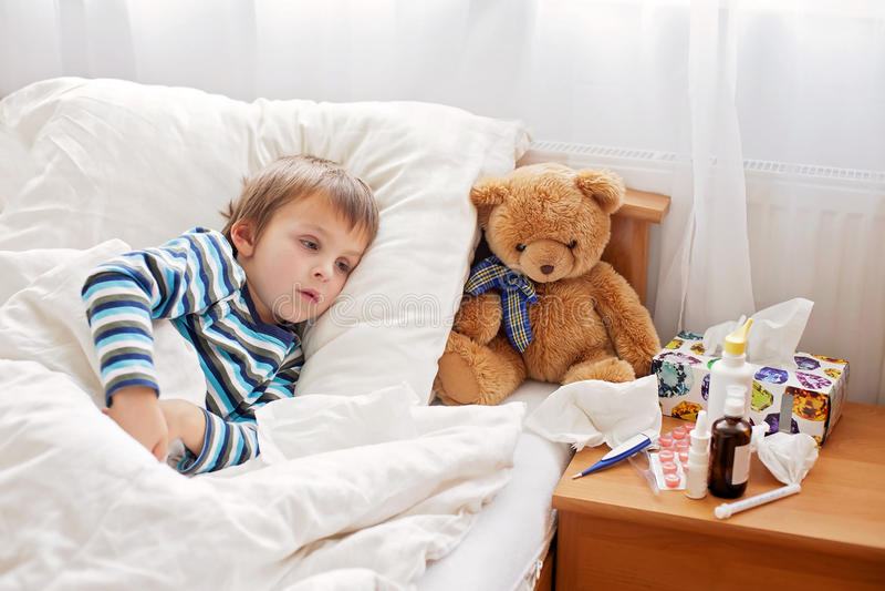Sjuk barnpojke som ligger i säng med en feber som vilar royaltyfri bild