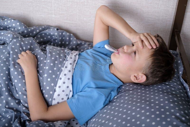 sjuk barnpojke som ligger i säng med en termometer arkivbilder