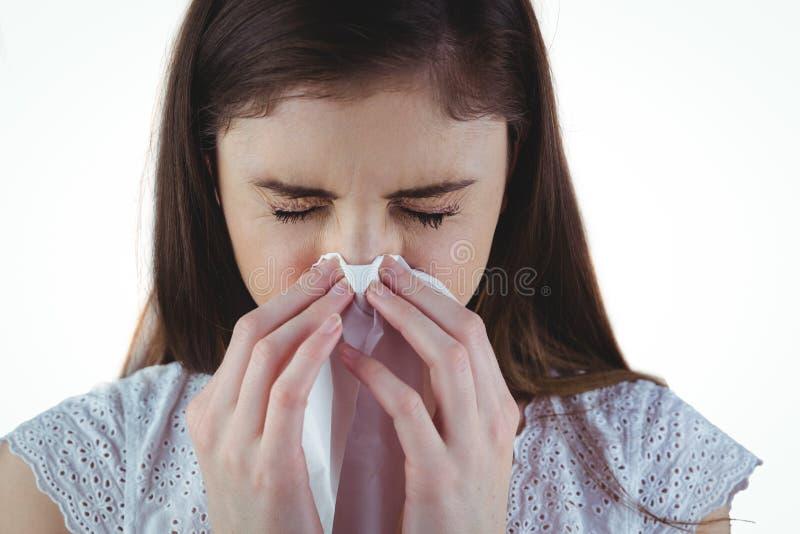 Sjuk brunett som blåser hennes näsa royaltyfri bild