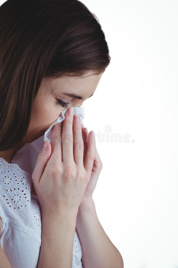 Sjuk brunett som blåser hennes näsa arkivbild