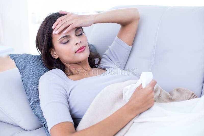 Sjuk brunett som ligger på soffan royaltyfri foto