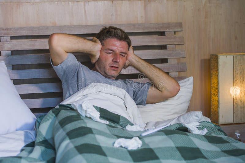 Sjuk för slösad och utmattad säng för man som förkylning och influensa för känsla hemma liggande opasslig lida nyser näsan med si royaltyfri foto