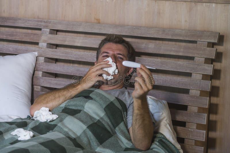 Sjuk för slösad och utmattad säng för man som förkylning och influensa för känsla hemma liggande opasslig lida nyser näsan med si arkivfoton