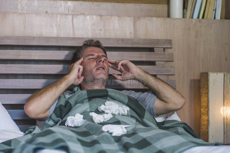 Sjuk för slösad och utmattad säng för man som förkylning och influensa för känsla hemma liggande opasslig lida nyser näsan med si arkivbilder