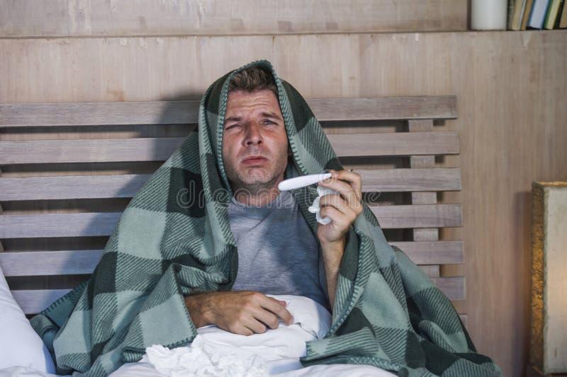 Sjuk för slösad och utmattad säng för man som förkylning och influensa för känsla hemma liggande opasslig lida nyser näsan med si royaltyfria bilder