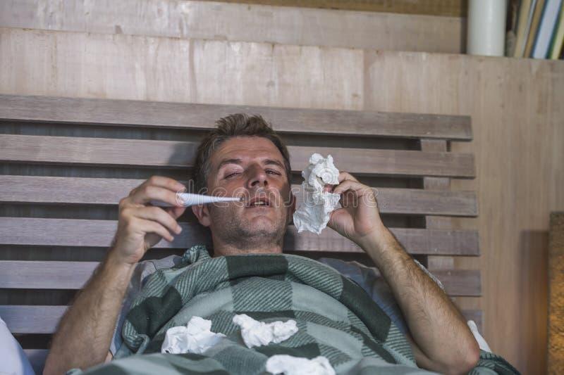 Sjuk för slösad och utmattad säng för man som förkylning och influensa för känsla hemma liggande opasslig lida nyser näsan med si royaltyfri fotografi