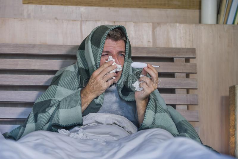 Sjuk för slösad och utmattad säng för man som förkylning och influensa för känsla hemma liggande opasslig lida nyser näsan med si arkivfoto