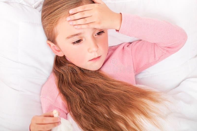 Sjuk flicka som ligger i säng med en termometer i mun arkivfoto