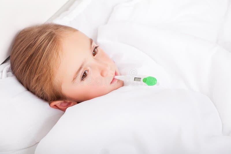 Sjuk flicka som ligger i säng med en termometer i mun arkivfoton