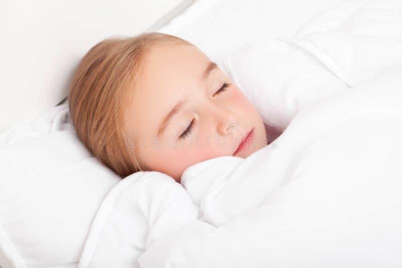 Sjuk flicka som ligger i säng med en termometer i mun royaltyfri foto
