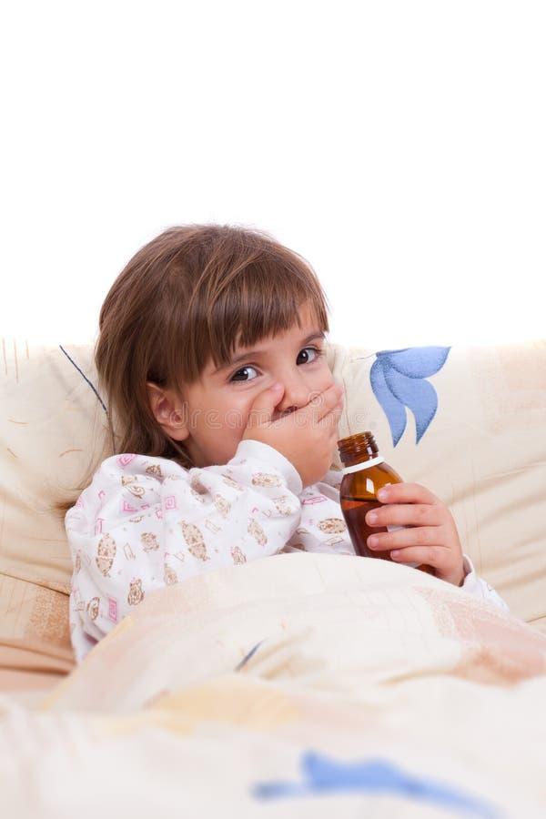 Sjuk flicka som ligger i underlag- och drinksirap royaltyfri foto