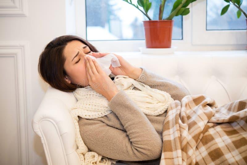 Sjuk flicka som ligger på soffan med en rinnande näsa royaltyfri fotografi