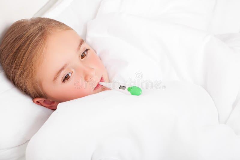 Sjuk flicka som vilar i säng med meassuring temperatur för feber med arkivbilder