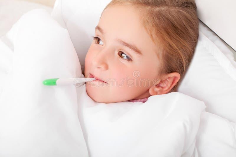 Sjuk flicka som vilar i säng med meassuring temperatur för feber med arkivbild