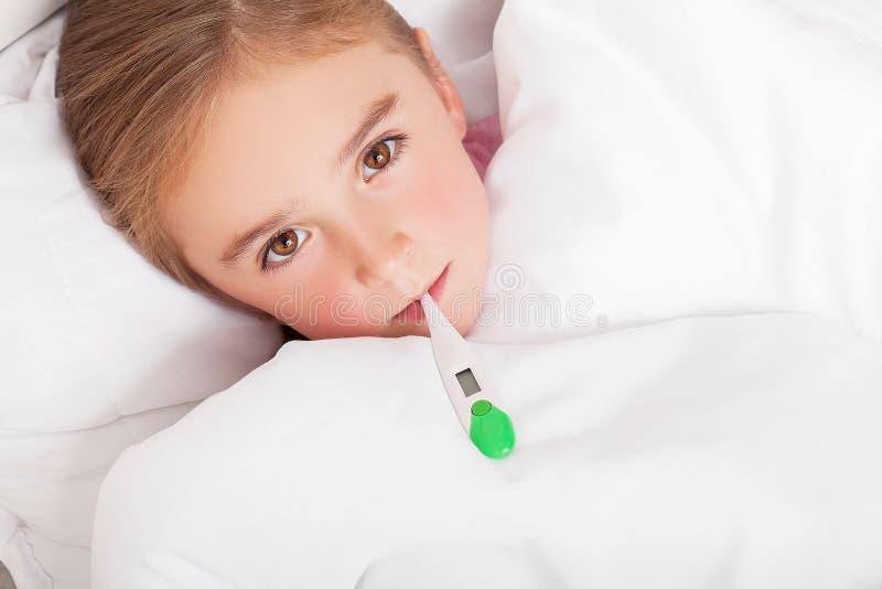Sjuk flicka som vilar i säng med meassuring temperatur för feber med royaltyfri fotografi