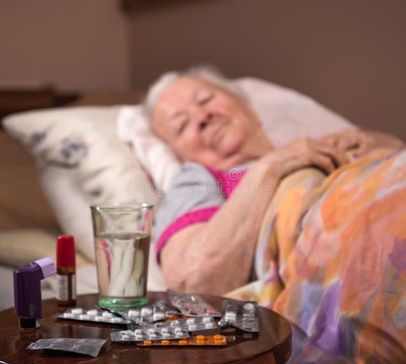 Sjuk gammal kvinna som hemma ligger i säng royaltyfria bilder