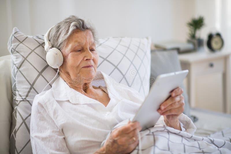 Sjuk hög kvinna med hörlurar och minnestavlan som hemma ligger i säng eller i sjukhus arkivfoto