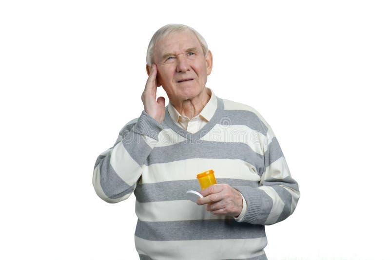 Sjuk hög man med huvudvärk och flaska av preventivpillerar royaltyfria bilder