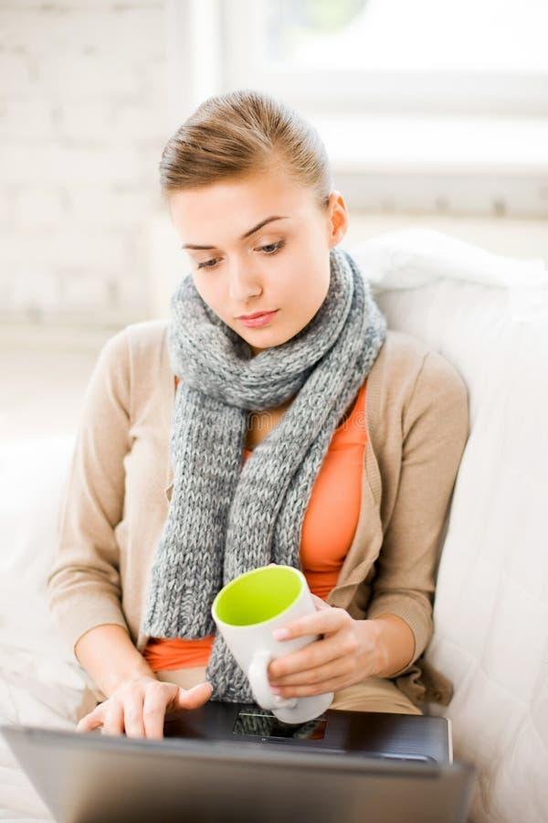 Sjuk kvinna i halsduk genom att använda bärbara datorn hemma arkivfoton