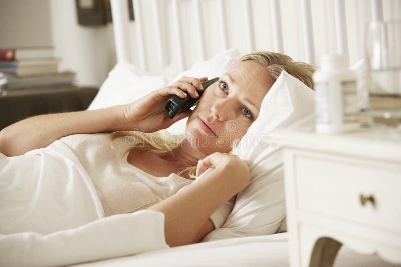 Sjuk kvinna i hemmastatt samtal för säng på telefonen arkivfoto