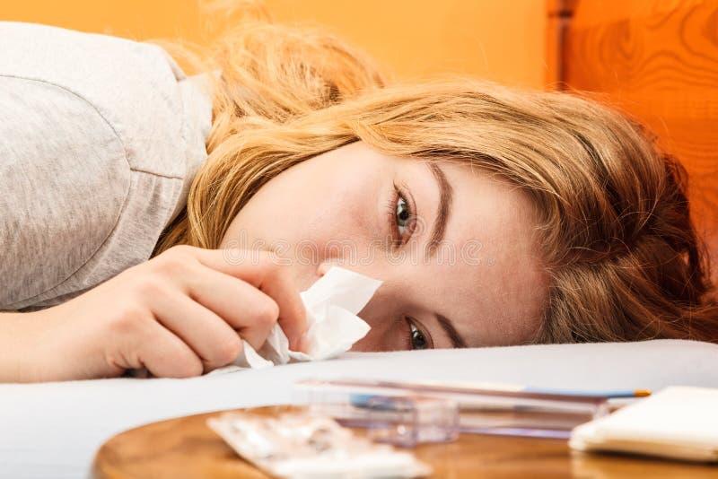 Sjuk kvinna i säng som nyser i silkespapper kallt fotografering för bildbyråer